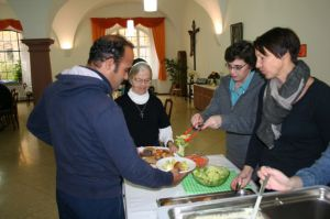 Sr. Kim sharing a meal with one of the many people seeking asylum